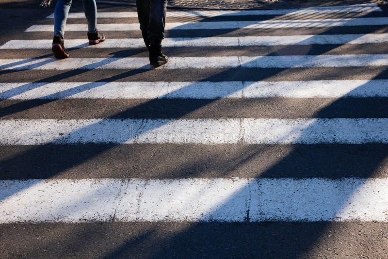 Stäng sig upp zebramarkering förgrundsgångare skuggar länge föreningspunktgatafot fotografering för bildbyråer