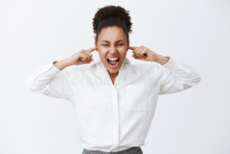 Stäng upp alla Stående av den intensiva bekymrade kvinnliga afrikansk amerikanaffärskvinnan i den vita skjortan som ropar medan royaltyfria foton