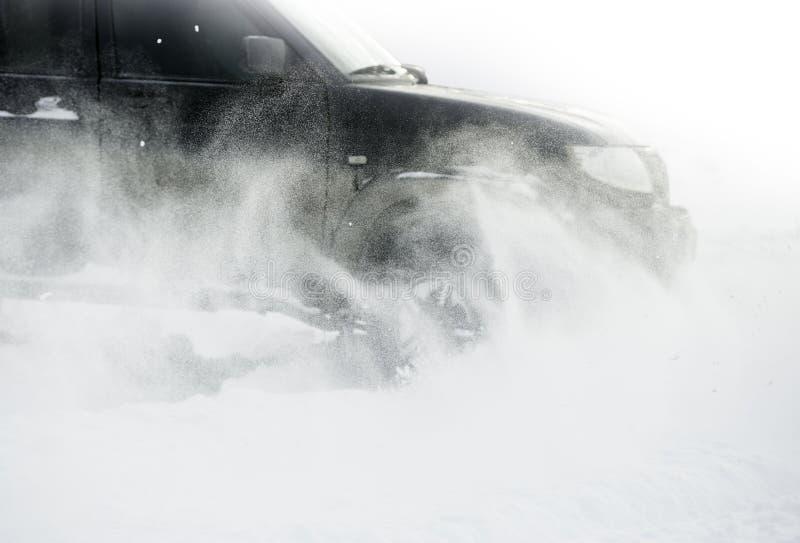 Stäng upp av bilgummihjul på en snöig väg (fokusen på snön) royaltyfria foton