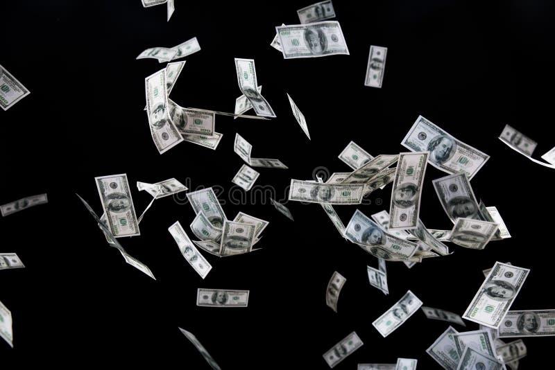 Stäng upp av oss dollarpengar som flyger över svart arkivbilder