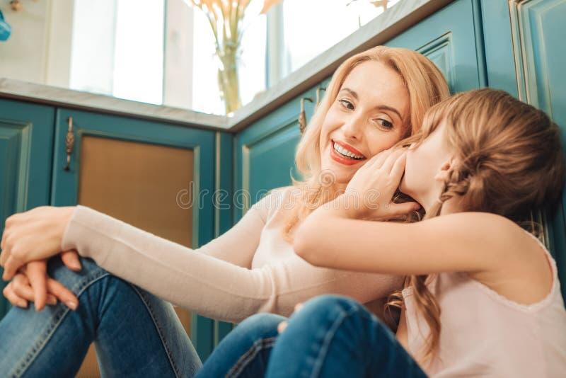Stäng upp av ung mamma det lyssna till hennes barn royaltyfri bild