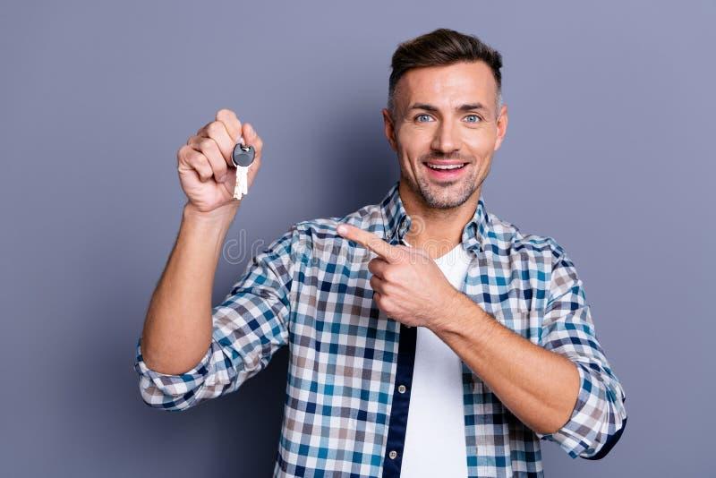 Stäng upp det stiliga fotoet honom honom hans grabbarmhänder som rymmer för mäklaremedel för nyckel- kedja rabatterat pris för fö arkivfoto