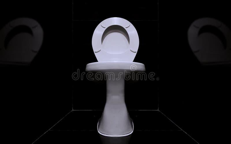 Stäng upp till en vit sanitär ware i ett mörkt toalettrum arkivfoton
