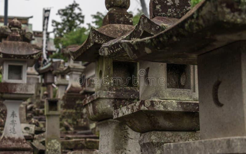 Stäng upp till många olika stenlyktor på vägen till en buddistisk tempel i Japan Higo Honmyo tempel, Kumamoto prefektur, Japan royaltyfri foto