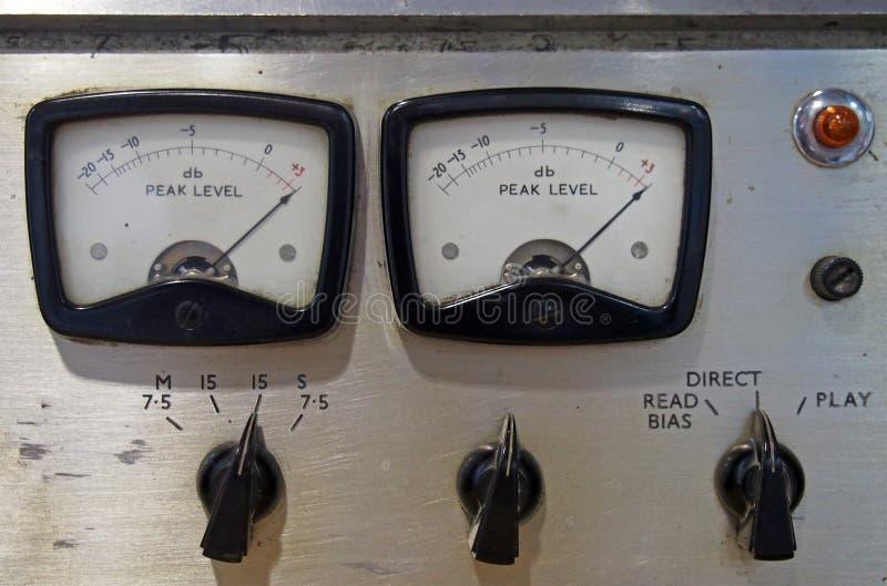 Stäng upp två gamla decibelmeter på en gammal vintage-rulle för att rulla bandspelare med kontrollknappar och omkopplare arkivbilder