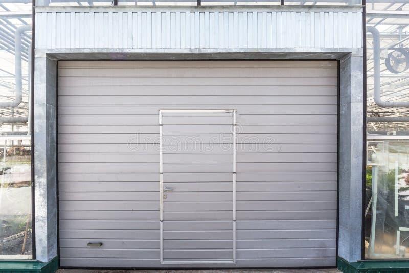 Stänga med fönsterluckor dörren eller rulldörren i växthusbyggnadsfasad royaltyfri foto
