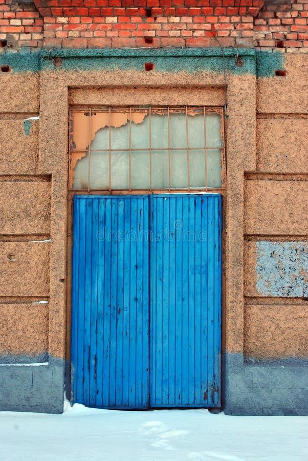 Stängd blå målad dörr, sprucken rosa murbruk på väggen för röda tegelstenar, grungebakgrund royaltyfria foton