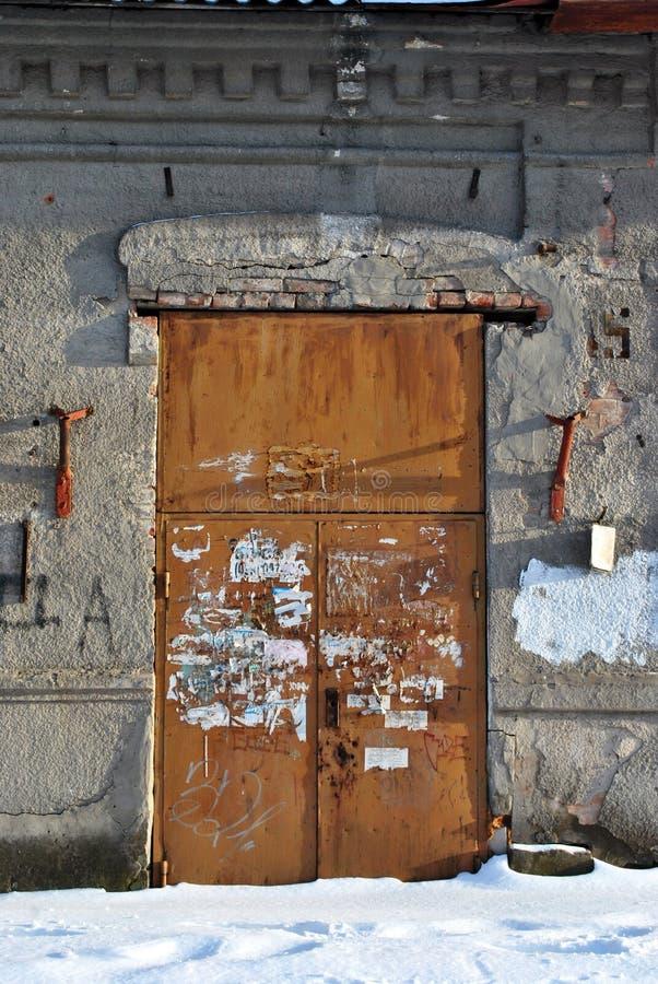Stängd brun målad dörr med sönderrivet annonspapper i som igenkännliga enda separata bokstäver, grå murbruk på väggen, grungebakg arkivfoto