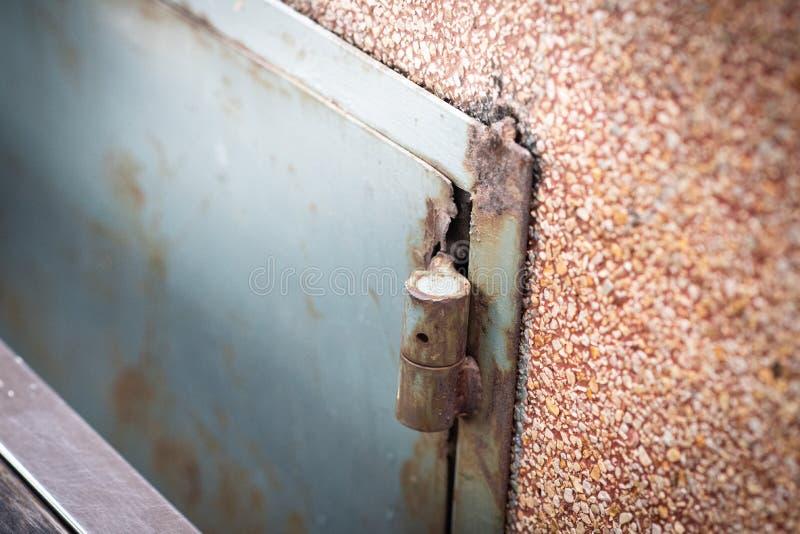 Stängd dörr för gammalt blått metallstål med röd rostig grunge på den orange modellväggen fotografering för bildbyråer