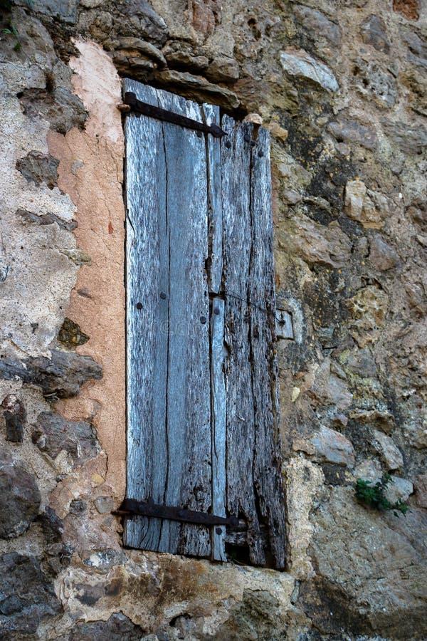 Stängd gammal yttre timmerfönsterslutare i lantlig stenvägg S royaltyfri bild