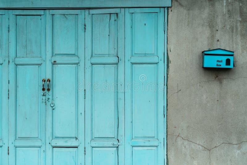 Stängd grön eller blå trädörr och tom brevlåda på den spruckna betongväggen av huset Gammalt hem med den spruckna cementväggen Ta royaltyfri fotografi