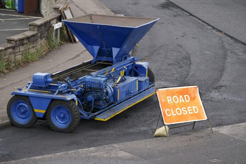 Stängd tecken och reparation för väg till tjäraasfaltgatan med den blåa maskinen fotografering för bildbyråer