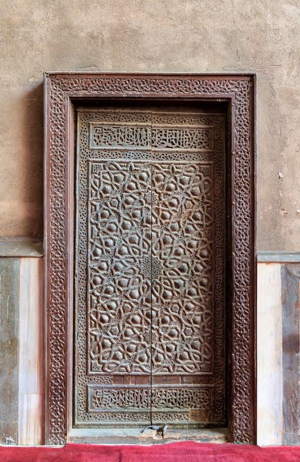 Stängd träåldrig dörr med utsmyckade bronzfärgade geometriska modeller royaltyfri bild