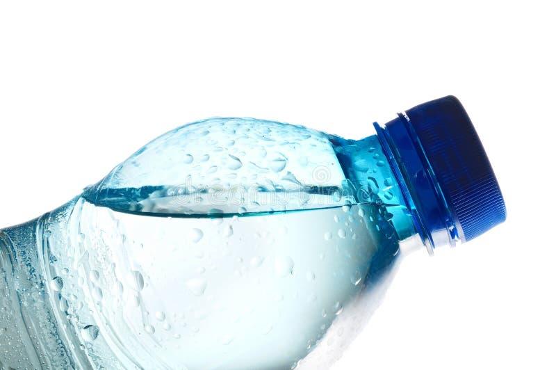 Stängd vattenflaska som fylls med vatten royaltyfria foton