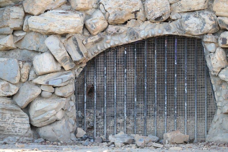 Stängda Rocky Cave med järnstänger arkivbilder
