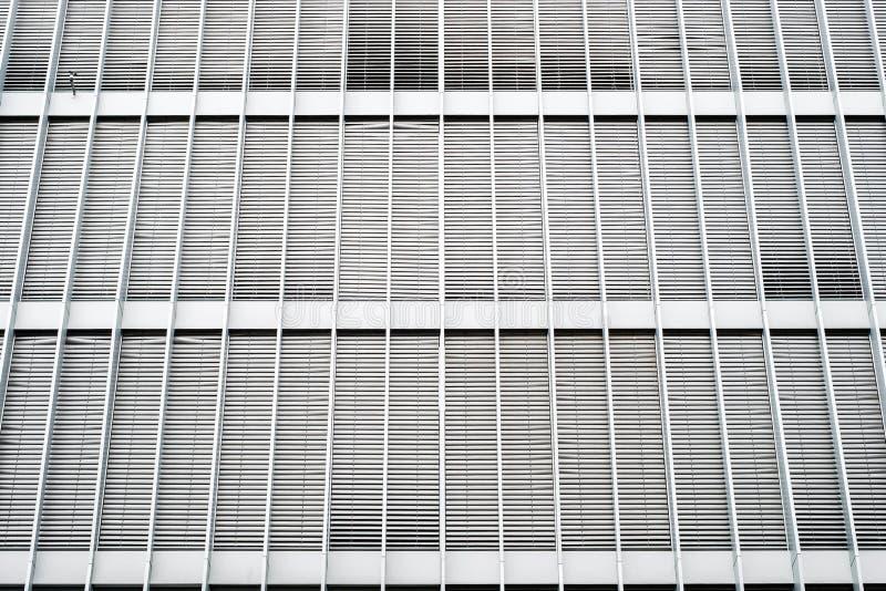 Stängda rullgardiner på modern byggande fasad, stängde slutare på kontorsyttersida royaltyfri bild