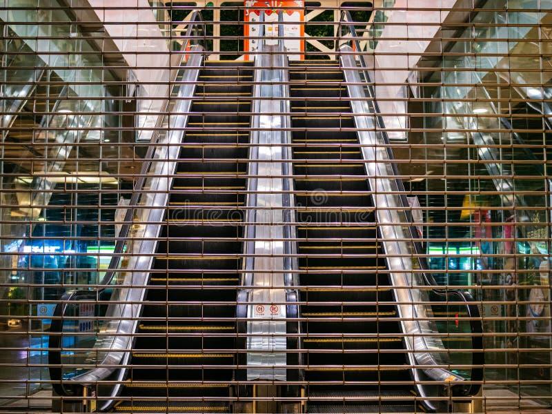 Stängda rulltrappor som igenom ses en stängd med fönsterluckor ingång till ett varuhus i det Tianhe området, Guangzhou, Kina royaltyfria bilder