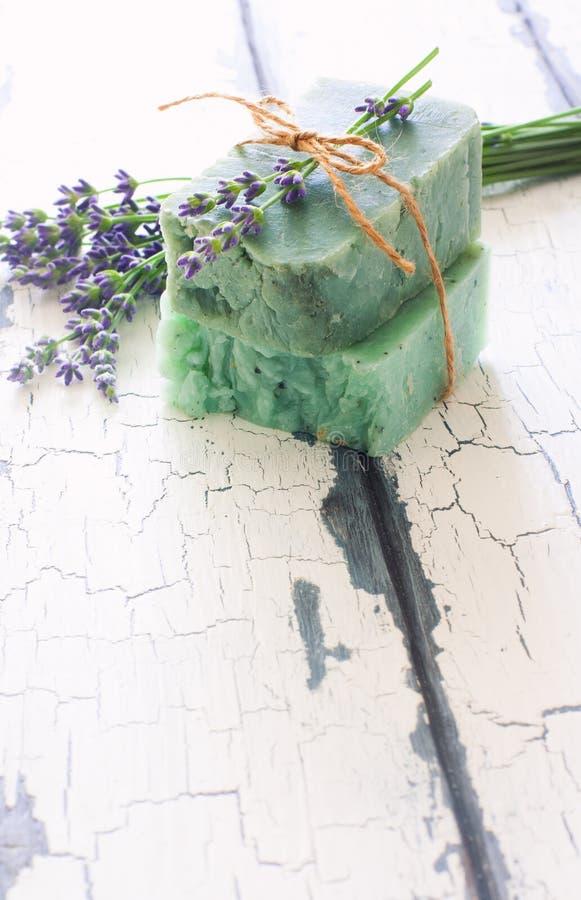 Stänger av handgjord tvål med lavendel blommar över vit wood grun royaltyfri foto