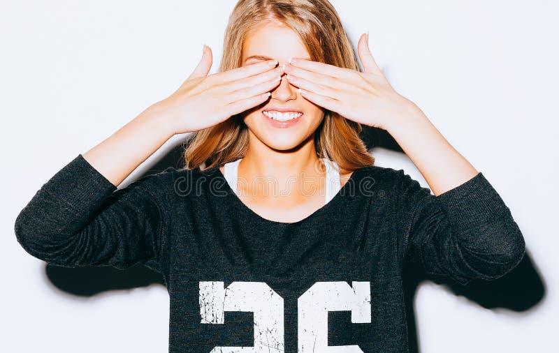 Stänger den härliga blonda galna flickan för den roliga livsstilståenden ögon med hennes händer, i tröja- och vitkortslutningar o royaltyfri bild