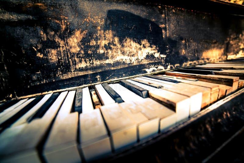 Stänger sig gamla pianotangenter för bruten grunge upp royaltyfria bilder