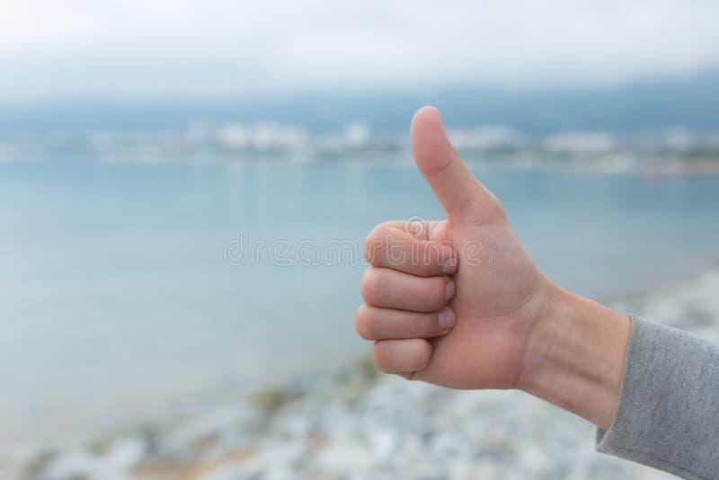 Stängning av handjur som visar tummarna mot havsbakgrund arkivfoto