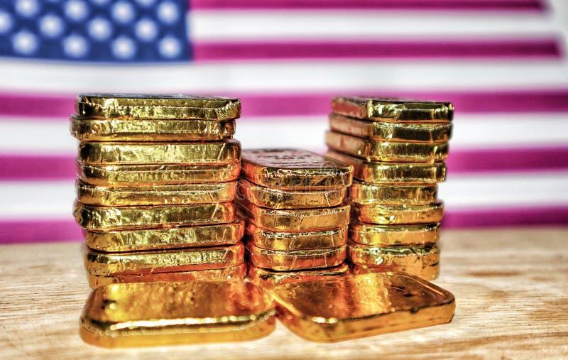 Stängning av många guldstaplar som är staplade på en bakgrund Förenta staternas flagg Begreppet guldmarknad Vintage-ton royaltyfri bild