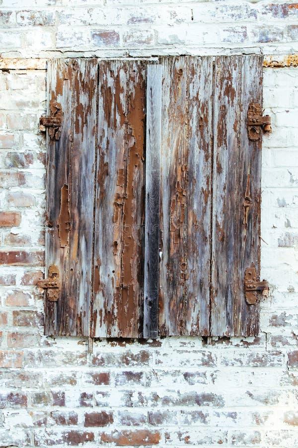 Stängt brunt rött skalande träfönster med rostade metallgångjärn på en grungy vit tegelstenvägg av en gammal övergiven övergiven  fotografering för bildbyråer