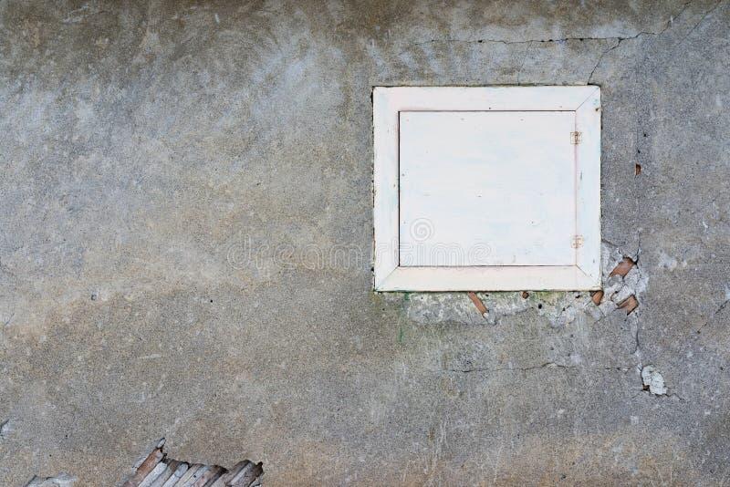 Stängt enkelt träfönster på det övergav huset som smular väggar arkivfoton