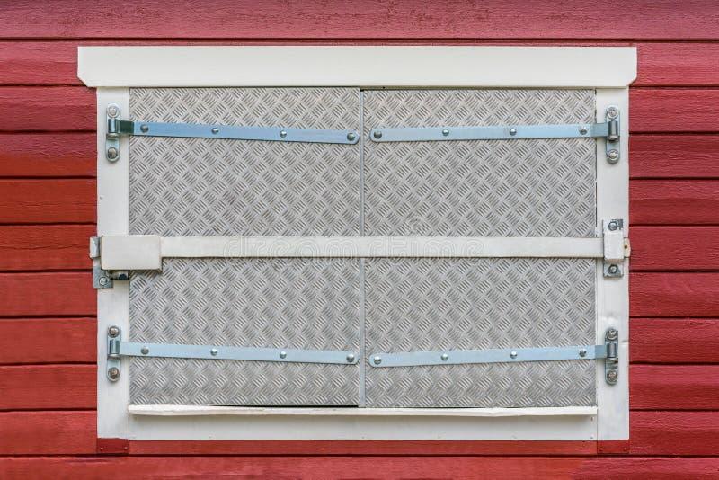 Stängt fönster på den röda yttre wood väggen med säkerhetsmonterings-, stång-, lås- och metallslutare royaltyfri foto
