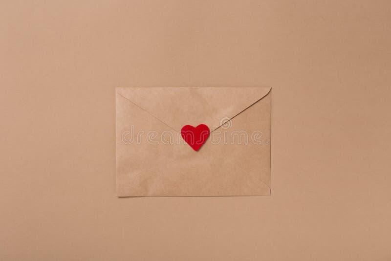 Stängt hantverkkuvert med röd hjärta på beige bakgrund Förälskelse arkivfoton