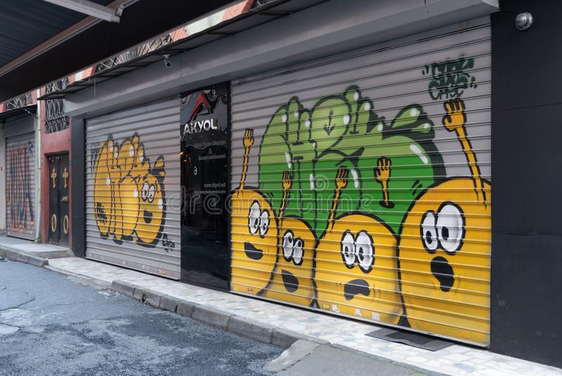 Stängt shoppa yttersida med rullande dörrar för metall som målas med färgrika grafitti på Hoca Tahsin Street, Karakoy, Istanbul,  royaltyfri foto