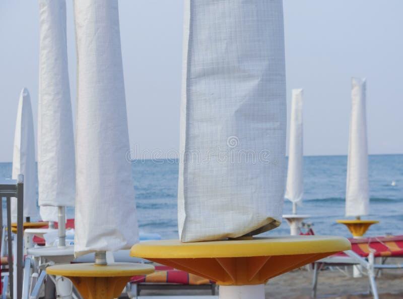 Stängt strandparaply på aftonen länge en italiensk strand i sommar royaltyfri foto