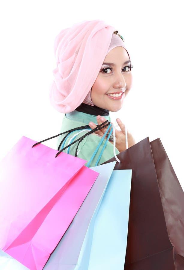 Stängt upp av den härliga muslimkvinnan som rymmer några shoppingpåsar royaltyfri foto