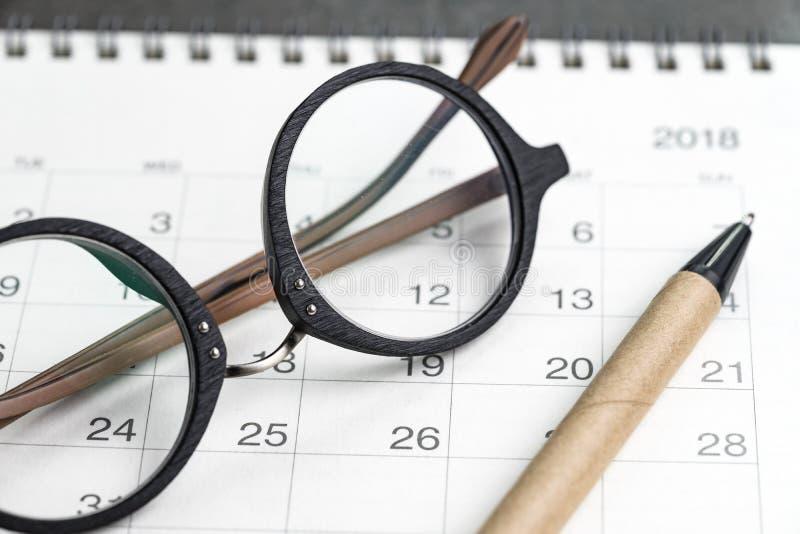 Stängt upp av glasögon och penna på kalender genom att använda som datumorgain royaltyfria foton