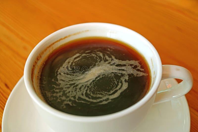 Stängt upp en kopp av varmt Americano kaffe tjänade som på trätabellen arkivfoton