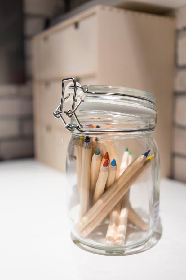 Stängt upp färgblyertspennor i den glass kruset med locket på det vita skrivbordet arkivfoto