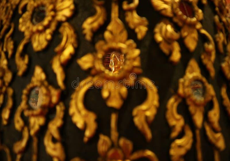 Stängt upp framsidan av den guld- Buddhabilden som reflekterar på spegeln av teakträt, målade pelaren i Wat Phumin Temple, Thaila fotografering för bildbyråer