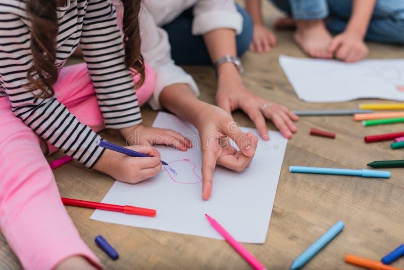 Stängt upp händer av mamman som undervisar små barn till att dra carto fotografering för bildbyråer