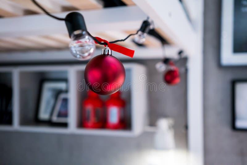 Stängt upp röda julbollar som hänger på ljus kula för svart rad arkivbilder