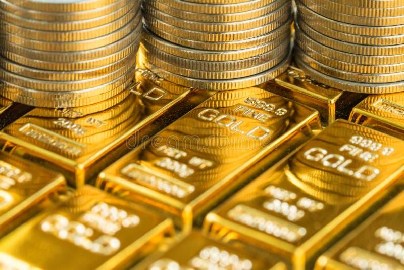 Stängt upp skottet av skinande guld- stänger med bunten av mynt som affär royaltyfri foto