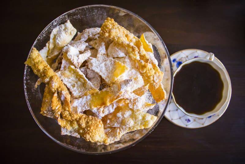 Stänk med pudrat socker, stekt platta av shortcakedeg Polsk kokkonst - faworkiängelvingar arkivbilder