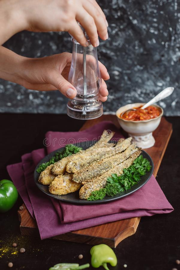 Stänket för händer för kock` s med den smaktillsats stekte fisken i en platta med tomatsås, gör grön och pepprar på träbräde och  royaltyfri fotografi