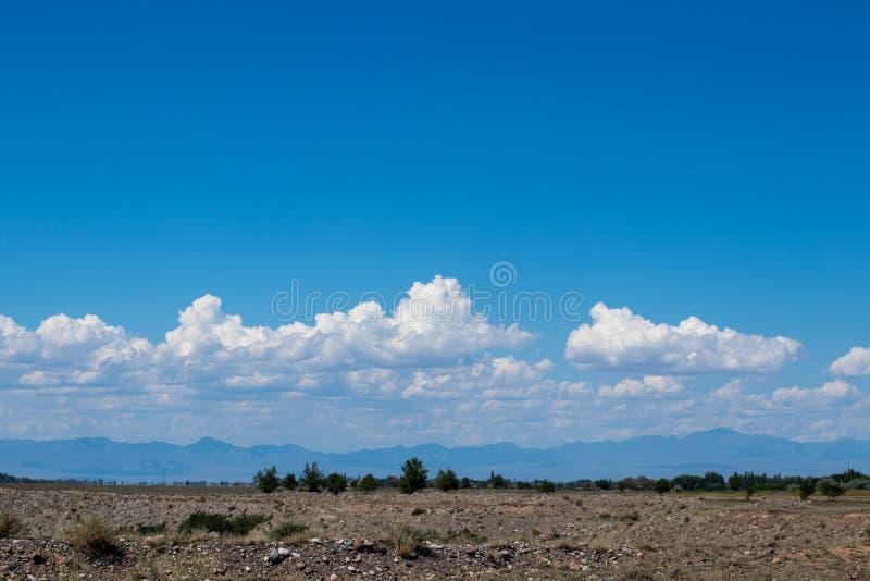 Stäpplandskap av Kasakhstan Himmel med moln ?ver bergen fotografering för bildbyråer
