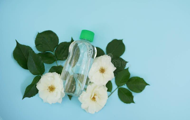 Stärkande vatten på blå bakgrund med rosor för vita blommor, kopieringsutrymme, naturliga organiska skönhetsmedel, kroppomsorg arkivbild