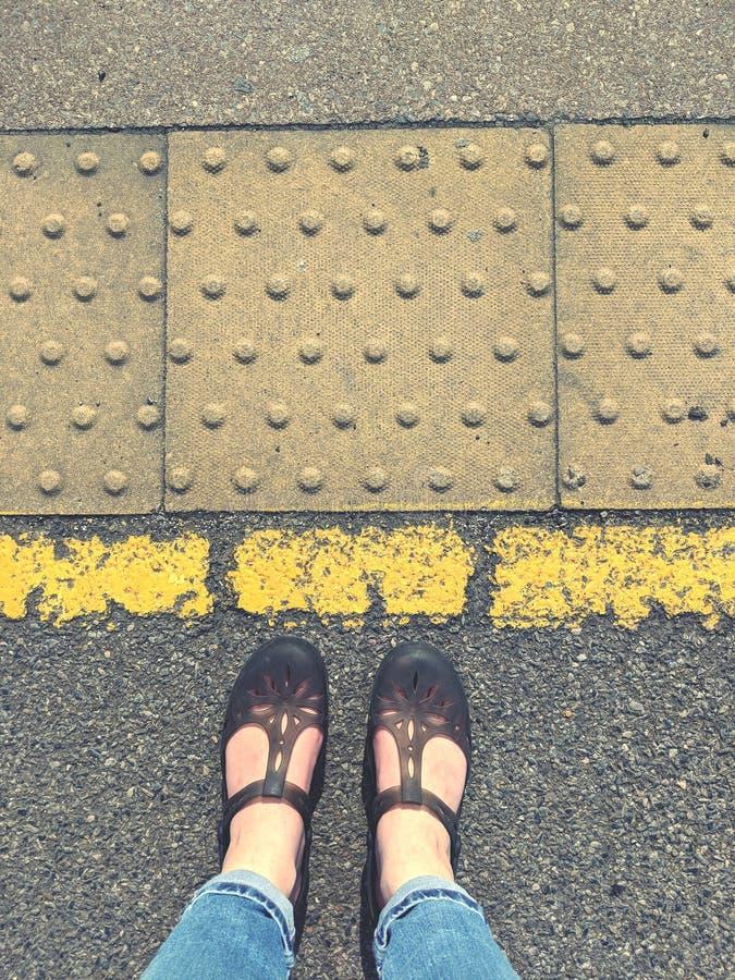 Stå bak den gula linjen med sandaler arkivbild