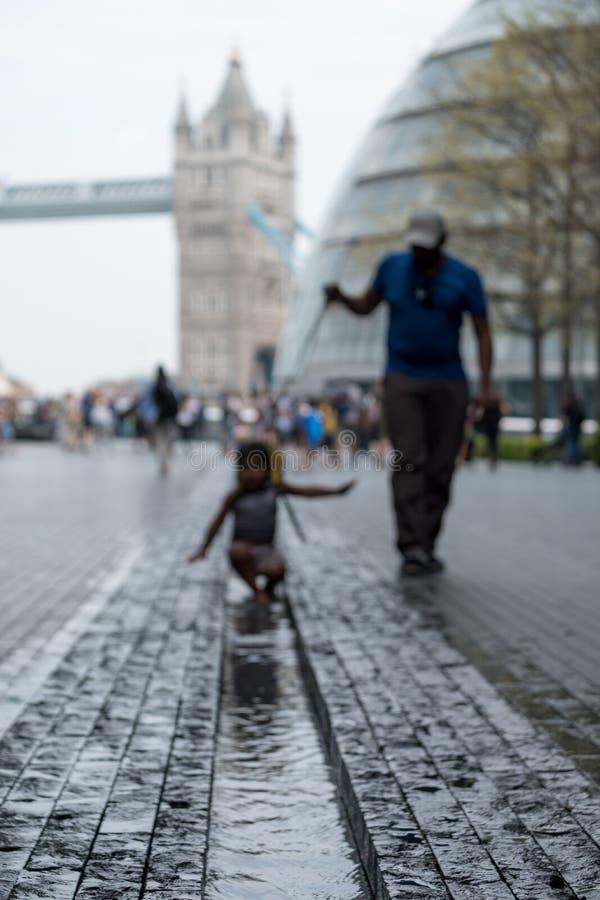 Stå högt bron i bakgrunden som tas på mer London på den södra banken I förgrunden är ett suddigt barn som spelar i vatten royaltyfria bilder