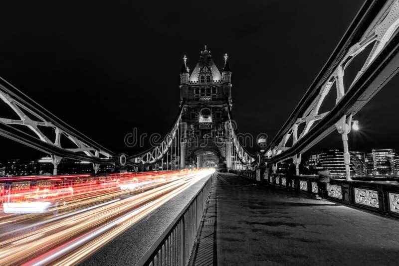 Stå högt bron i London i svartvitt, UK på natten med suddighet färgade billjus arkivfoton