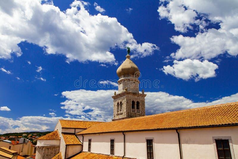 Stå högt med en kupol, tak av hus mot en blå himmel med moln i Kroatien arkivfoton