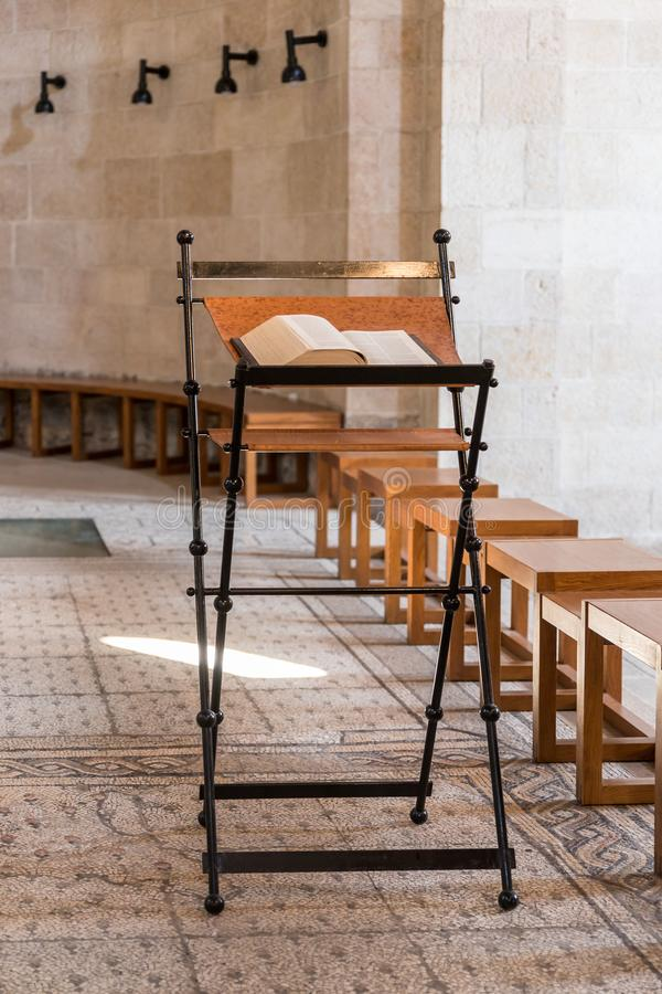 Stå med en öppen bibel i den centrala korridoren i Tabgha - katolsk kyrkamultiplikationen av bröd och fisken som lokaliseras på k arkivbild
