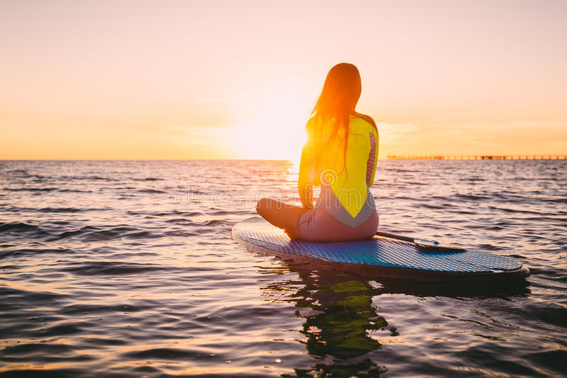 Stå upp skovellogi på ett tyst hav med varma sommarsolnedgångfärger Koppla av på havet arkivfoto